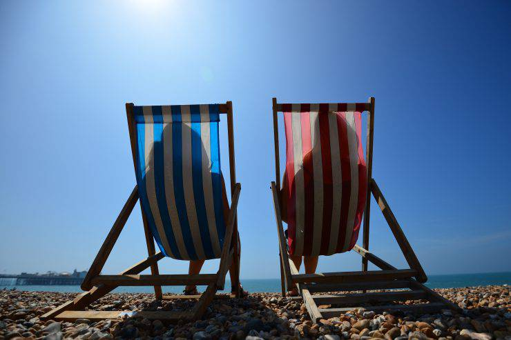 People relax in deck chairs on the beach in Brighton on July 18, 2014, as parts of the country were expected to experience the hottest day of the year so far and the Met Office issued a heatwave alert for southern England and the Midlands.  AFP PHOTO / CARL COURT        (Photo credit should read CARL COURT/AFP/Getty Images)