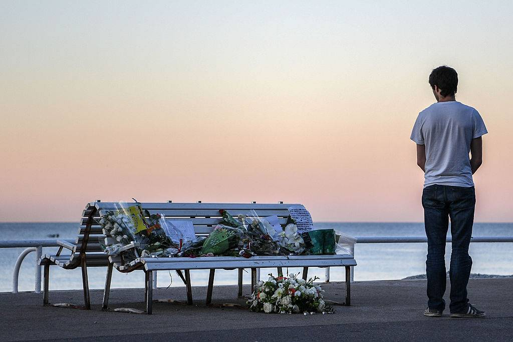 NICE, FRANCE - JULY 17: A man looks at a tribute laying on a bench near where a person was killed on the Promenade des Anglais on July 17, 2016 in Nice, France. Six people believed to be linked to the man who killed 84 people in Nice are in police custody according to a statement by the Paris prosecutor's office after a French-Tunisian attacker killed 84 as he drove a lorry through crowds, gathered to watch a firework display during Bastille Day Celebrations. The attacker then opened fire on people in the crowd before being shot dead by police. (Photo by David Ramos/Getty Images)