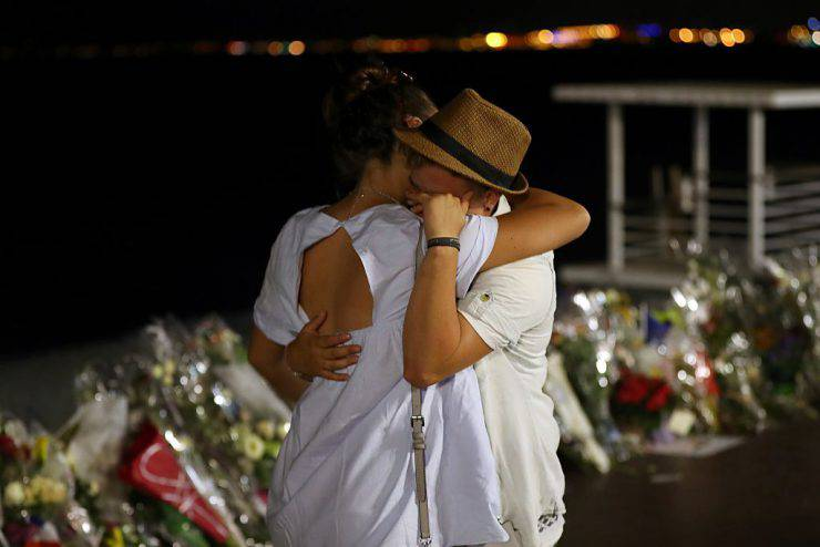 Two people hold each other by the new makeshift memorial on July 18, 2016 in Nice, in tribute to the victims of the deadly Bastille Day attack at the Promenade des Anglais after it was moved from the pavement of the road to the seafront so that the street can be re-opened. France was set to hold a minute's silence on July 18, 2016 to honour the 84 victims of Mohamed Lahouaiej-Bouhlel, a 31-year-old Tunisian who drove a truck into a crowd watching a fireworks display on Bastille Day, but a period of national mourning was overshadowed by bickering politicians. Church bells will toll across the country, and the country will fall silent at midday, a now grimly familiar ritual after the third major terror attack in 18 months on French soil. / AFP / Valery HACHE (Photo credit should read VALERY HACHE/AFP/Getty Images)
