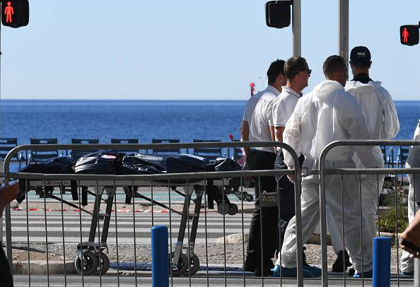 "Forensics experts evacuate a dead body on the Promenade des Anglais seafront in the French Riviera town of Nice on July 15, 2016, after a gunman smashed a truck into a crowd of revellers celebrating Bastille Day. An attack in Nice where a man rammed a truck into a crowd of people left 84 dead and another 18 in a ""critical condition"", interior ministry spokesman Pierre-Henry Brandet said on July 15. An unidentified gunman barrelled the truck two kilometres (1.3 miles) through a crowd that had been enjoying a fireworks display for France's national day before being shot dead by police. / AFP / BORIS HORVAT (Photo credit should read BORIS HORVAT/AFP/Getty Images)"