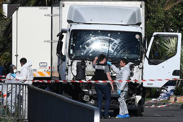 "Forensics officers and policemen look for evidences near a truck on the Promenade des Anglais seafront in the French Riviera town of Nice on July 15, 2016, after it drove into a crowd watching a fireworks display. An attack in Nice where a man rammed a truck into a crowd of people left 84 dead and another 18 in a ""critical condition"", interior ministry spokesman Pierre-Henry Brandet said Friday. An unidentified gunman barrelled the truck two kilometres (1.3 miles) through a crowd that had been enjoying a fireworks display for France's national day before being shot dead by police.  / AFP / ANNE-CHRISTINE POUJOULAT        (Photo credit should read ANNE-CHRISTINE POUJOULAT/AFP/Getty Images)"