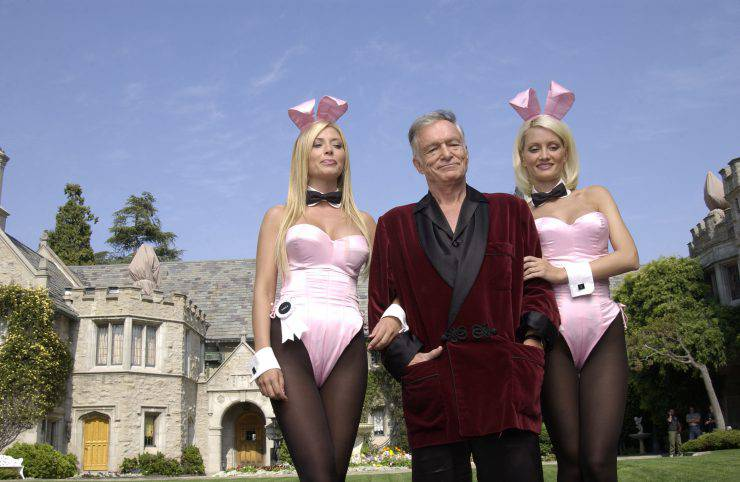 "HOLMBY HILLS, CA - MAY 6:  (L to R) Playboy bunny Sheila Levell, Playboy founder Hugh Hefner and Playboy bunny Holly Madison perform a scene during the filming of a commercial for ""X Games IX"" at the Playboy Mansion May 6, 2003 in Holmby Hills, California. This year's X Games will take place at STAPLES Center in Los Angeles from August 14th through 18th.  (Photo by Robert Mora/Getty Images)"