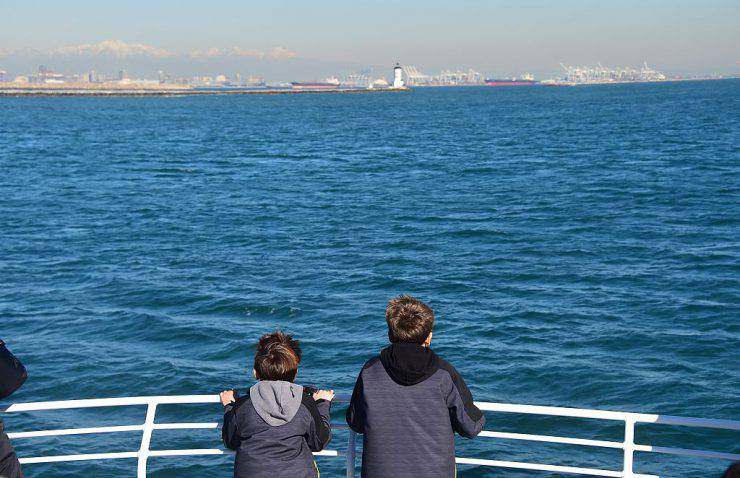 Boys lookout for whales in the Pacific Ocean off the southern California coastline on January 12, 2016, as the annual migration of the Gray Whale, which makes one of the longest migration routes of any mammal on earth, is underway. The mammals are making their way back north for the summer in the Pacific Ocean along the western North American coastline. In the distance is Angel's Gate Lighthouse which leads into San Pedro Harbour. AFP PHOTO/FREDERIC J. BROWN / AFP / FREDERIC J BROWN        (Photo credit should read FREDERIC J BROWN/AFP/Getty Images)