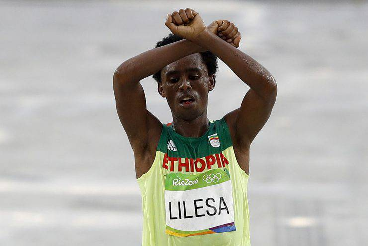 TOPSHOT - Ethiopia's Feyisa Lilesa (silver) crosses the finish line of the Men's Marathon athletics event during the Rio 2016 Olympic Games at the Sambodromo in Rio de Janeiro on August 21, 2016.   Lilesa crossed his arms above his head as he finished the race as a protest against the Ethiopian government's crackdown on political dissent.  / AFP / Adrian DENNIS        (Photo credit should read ADRIAN DENNIS/AFP/Getty Images)