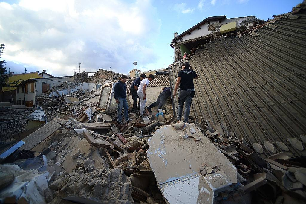 Residents and rescuers search for victims among damaged homes after a strong heartquake hit Amatrice on August 24, 2016. Central Italy was struck by a powerful, 6.2-magnitude earthquake in the early hours, which has killed at least three people and devastated dozens of mountain villages. Numerous buildings had collapsed in communities close to the epicenter of the quake near the town of Norcia in the region of Umbria, witnesses told Italian media, with an increase in the death toll highly likely. / AFP / FILIPPO MONTEFORTE        (Photo credit should read FILIPPO MONTEFORTE/AFP/Getty Images)