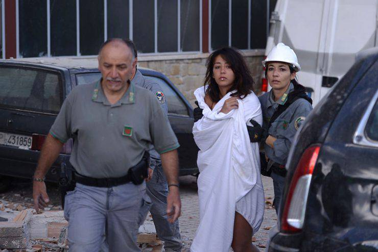 Rescuers help a woman among damaged buildings after a strong earthquake hit central Italy, in Amatrice on August 24, 2016. A powerful 6.2-magnitude earthquake devastated mountain villages in central Italy on Wednesday, leaving at least 18 people dead and dozens more injured or unaccounted for.  Scores of buildings were reduced to dusty piles of masonry in communities close to the epicentre of the pre-dawn quake in a remote area straddling the regions of Umbria, Marche and Lazio. / AFP / FILIPPO MONTEFORTE        (Photo credit should read FILIPPO MONTEFORTE/AFP/Getty Images)