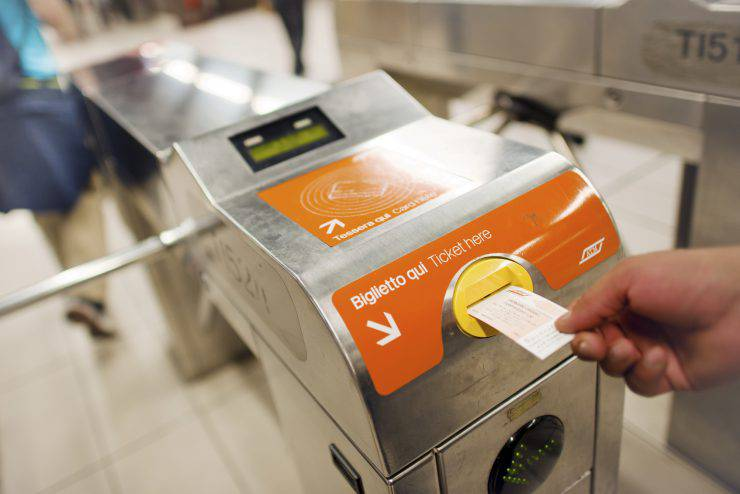 Milan, Italy - September 30, 2011: Man's hand swiping subway pass card over card reader on the gate of underground station in the center of Milan