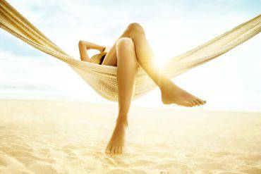 Woman relaxes in a hammock with bare feet.  Her feet and legs are featured in the foreground of the image.  One hand is raised to hold a straw hat on her head, though her face is not visible.  The hammock is hung at the beach with the sun shining from behind it.  The hammock is made of lightweight material, which the light passes through.  The sand is soft and has many footprints in it.  A strip of ocean is visible above the sand, and above that is the sky, which is bright blue and has some white clouds.