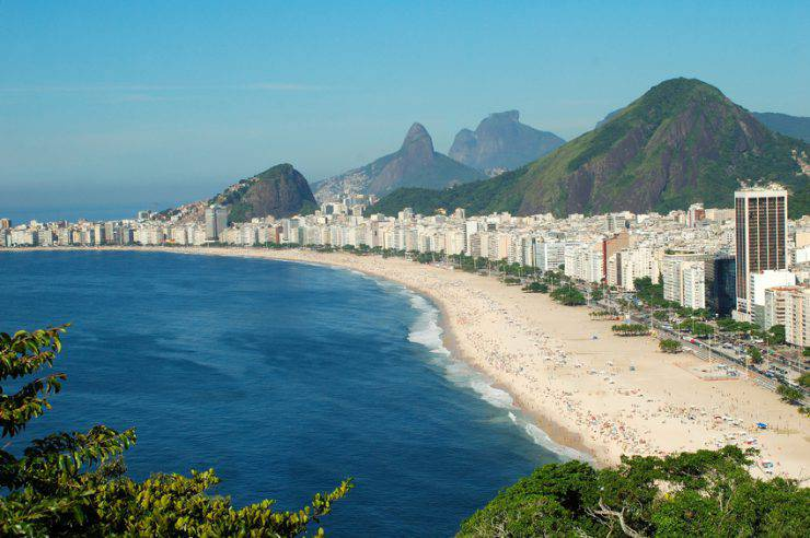View of Cobacabana beach days a lot of sun in the city with its line of apartments on the waterfront. In the background the hill da Gávea and the Two Brothers