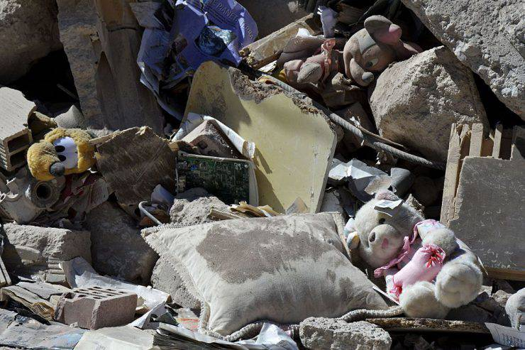 Children toys lay among rubble and debris of a destroyed building in the central Italian village of Amatrice, on August 28, 2016, four days after a 6.2-magnitude earthquake struck the region, killing nearly 300 people. Shoddy, price-cutting renovations, in breach of local building regulations, could be partly to blame for the high death toll from this week's devastating earthquake in central Italy, according to a prosecutor investigating the disaster. As questions mount over the deaths of nearly 300 people, prosecutor Giuseppe Saieva indicated that property owners who commissioned suspected sub-standard work could be held responsible for contributing to the quake's deadly impact.  / AFP / ANDREAS SOLARO        (Photo credit should read ANDREAS SOLARO/AFP/Getty Images)