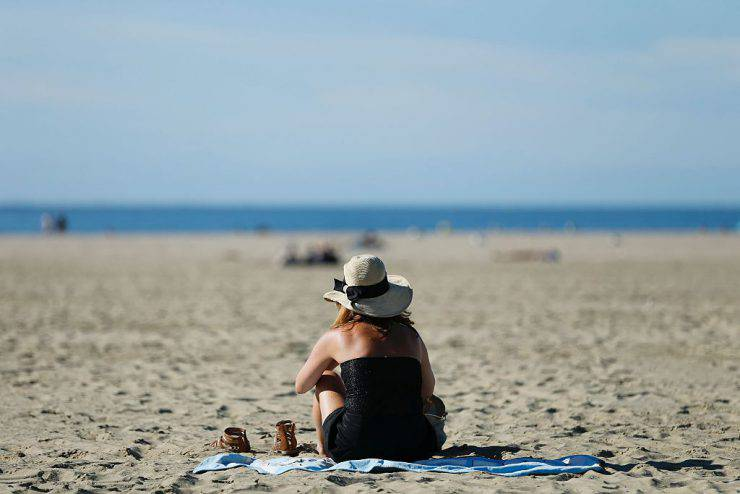 A woman sits on the beach in the northwestern sea resort of Deauville, on September 9, 2016. / AFP / CHARLY TRIBALLEAU (Photo credit should read CHARLY TRIBALLEAU/AFP/Getty Images)