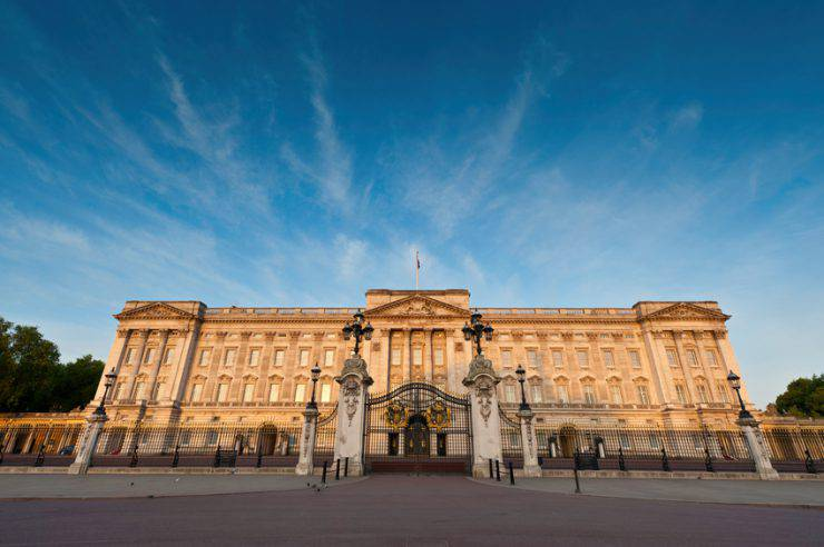"""London, UK - May 3rd, 2011: Warm dawn sunlight illuminated the warm stone facade, windows, balcony and ornate entrance gates of Buckingham Palace, London residence of the British Monarch, from the Victoria Memorial on The Mall."""