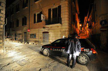 An Italian Carabinieri inspects the streets during a night patrol of the collapsed  buildings of the devastated city of L'Aquila on April 14, 2009, epicentre of the April 6 earthquake that stroke the Abruzzo region.  AFP PHOTO / ANDREAS SOLARO (Photo credit should read ANDREAS SOLARO/AFP/Getty Images)
