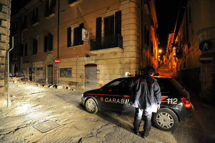An Italian Carabinieri inspects the streets during a night patrol of the collapsed buildings of the devastated city of L'Aquila