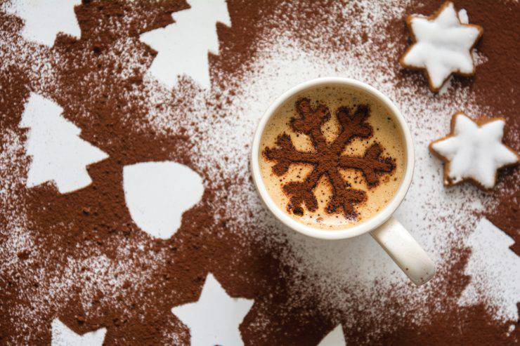 Hot drink with cocoa snowflake stencil