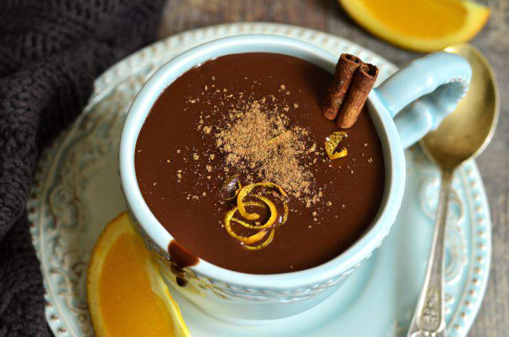 Homemade hot chocolate with orange and cinnamon in a vintage cup.
