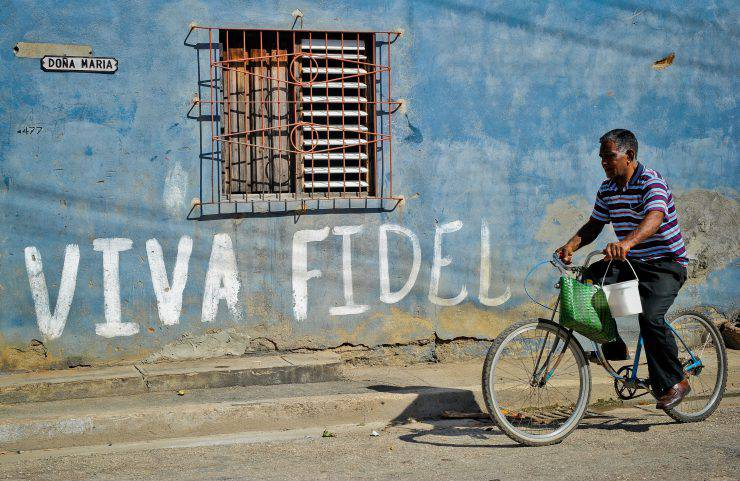 A Cuban rides his bicycle by a graffiti hailing Cuban former president Fidel Castro, on August 12, 2014 in Havana.  Fidel Castro will be 88 on Wednesday     AFP PHOTO/YAMIL LAGE   Fidel Castro will be 88 on Wednesday.       AFP PHOTO/YAMIL LAGE        (Photo credit should read YAMIL LAGE/AFP/Getty Images)