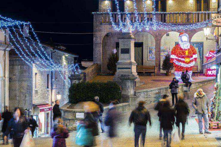 San Marino, San Marino - December 24, 2015: A large Santa Klaus made of lights welcomes visitors in the upper side of the old town of San Marino, where await a Christmas market and streets brightened by lights. People stroll in the street.