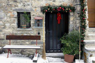Entrance of a small italian cottage with christmas decoration.