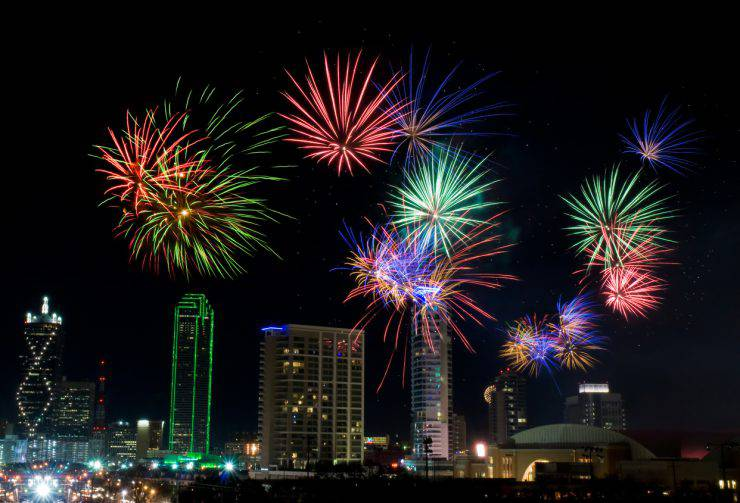 Colorful fireworks display in Dallas, Texas celebrating New Years Eve. Business district and office buildings in background.
