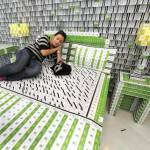 A woman poses on a bed made of key cards
