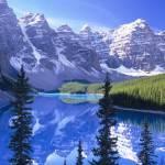 veduta lago tra montagne rocciose innevate