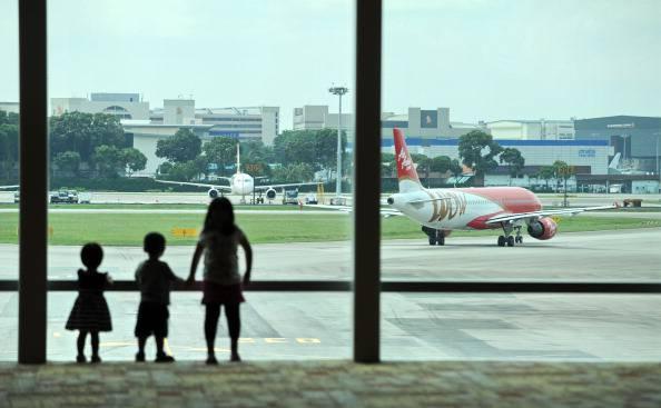 Children watch as an AirAsia plane leave