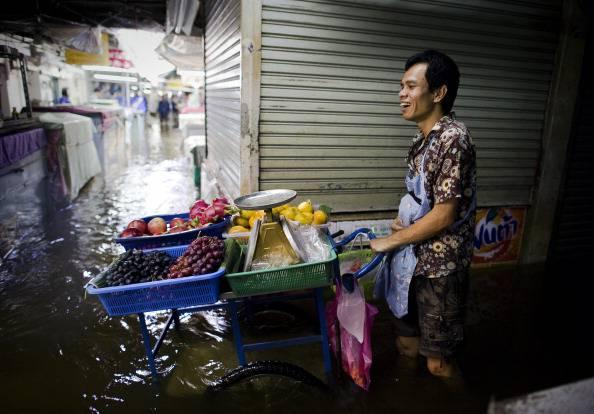 A fruit vendor push his cart through flo