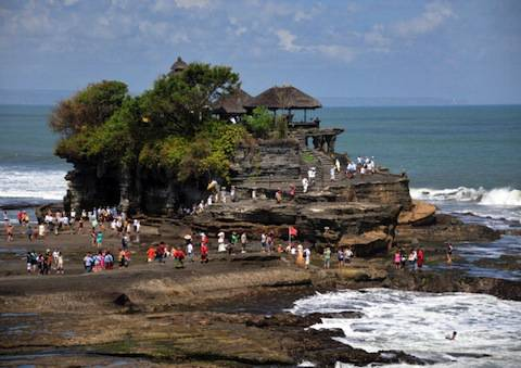 Foregin tourists look at Balinese people